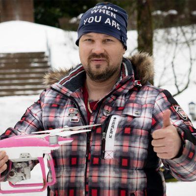 Mies pitää pinkkiä dronea kädessä