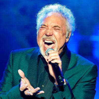 Tom Jones sjunger i en mikrofon som han håller i handen.
