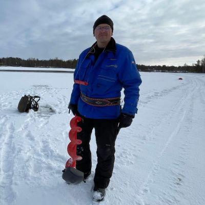 Nellimiläinen Aimo Koistinen mittaamassa jäätä Inarijärvellä huhtikuussa 2021.