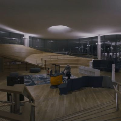 En bred bild inifrån biblioteket Ode på natten, lamporna lyser och en städare står mitt i bilden med en golvputsarmanick som han kör.