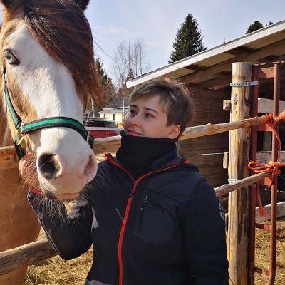 Ravivalmentaja Iida Lantto hevosen vieressä.
