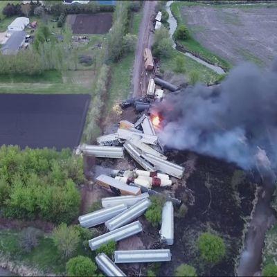 Flygbild på tågvagnar som ligger huller om buller och brinner.