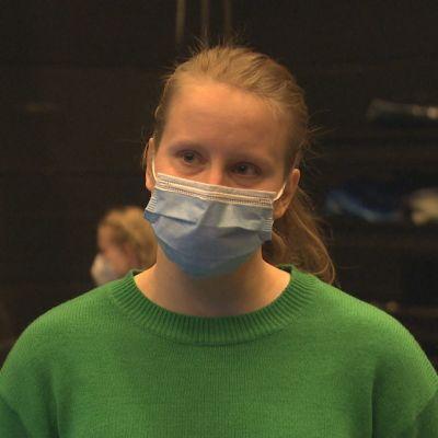 Charlotta Ingraeus i förgrunden med ansiktsskydd. I bakgrunden sitter ljudtekniker.