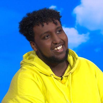 Hassan Maikal istuu Ylen Puoli seitsemän -ohjelman studiossa keltainen huppari päällään.