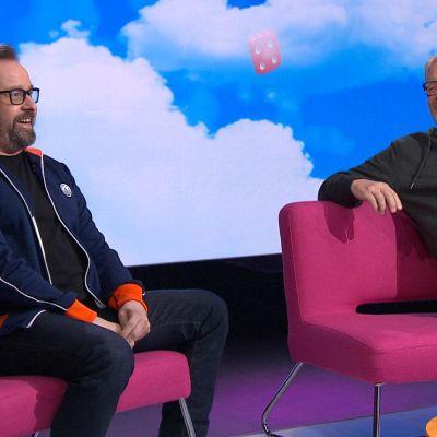 Heikki Hela ja Heikki Silvennoinen istuvat Puoli seitsemän -ohjelman sohvilla studiossa.