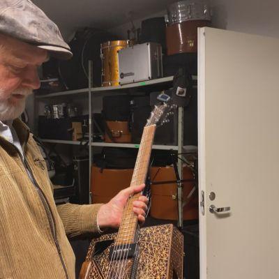 Tuomari Nurmio esittelee tärkeää instrumenttiaan, sikarilaatikko-kitaraa
