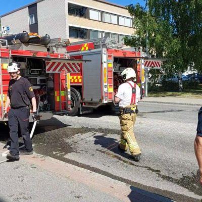 Paloautoja ja palomiehiä katuvarressa.