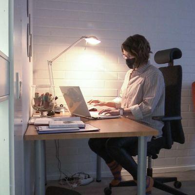 Kriisikeskuspäivystäjä työskentelee tietokoneella hämärässä huoneessa