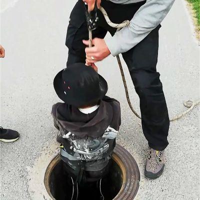 Mies nostaa valjaissa olevaa poikaa ylös sadevesikaivosta
