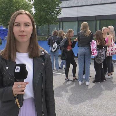 Toimittaja Lotta Sillanmäki seisoo festivaalialueella mikrofoni kädessä.