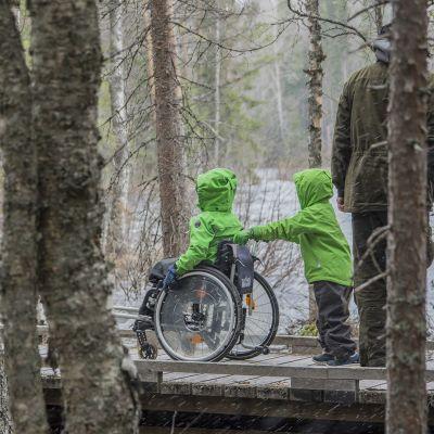 Lapsi työntää toista lasta pyörätuolissa esteettömällä retkeilyreitillä..