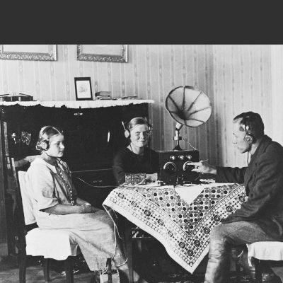 Radionkuuntelua 1920-luvulla.Kaksi naista ja mies pöydän ääressä kuuntelemassa radiota (kuulokkeet).
