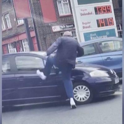 Mies potkii autoa bensa-asemalla Englannissa.