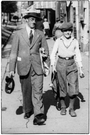 Isä ja poika, Elias ja Leo Kari kävelevät kadulla Viipurissa noin 1935. Pojalla on kädessä auton ratti.