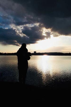 Oopperalaulaja Waltteri Torikka dramaattisessa ilta-aurinkomaisemassa.