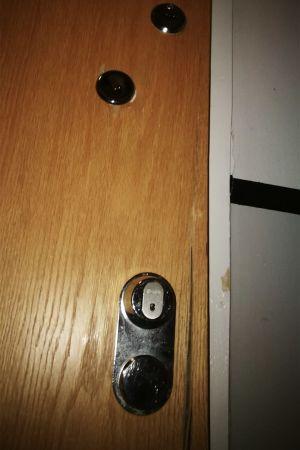 En ytterdörr i trä. Dörrkanten har spruckit, och listen bredvid dörren har lossnat.