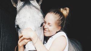 En ung kvinna kramar med slutna ögon sin hästs mule. Hästen är silvergrå.