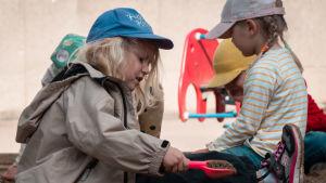 Två barn sitter i en sandlåda och leker. En flicka håller i en röd spade med sand i.
