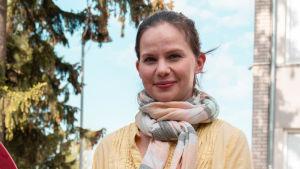 Porträtt av Kristina Hyvärinen som står ute i en park.