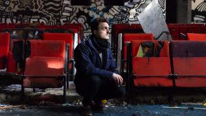 Viktor Granö på huk i ett utrymme med röda bänkar och graffiti samt skrot på marken