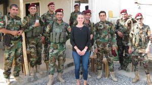 Mariette Hägglund står tillsammans med en grupp Peshmergasoldater vid en frontlinje mot IS (2017).