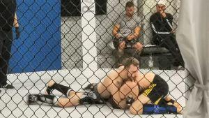 Två män ligger på golvet och kämpar mot varandra i MMA