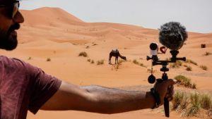 En man håller i en filmkamera mot en kamel i öknen