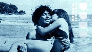 Kuvassa jalkapalloilija Diego Maradona pitelemässä naista sylissään ja kävelemässä hiekkarannalla.