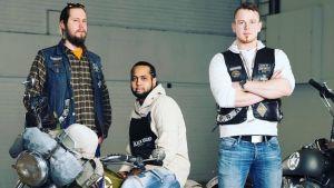 kolme nuorta miestä joista yksi istuu moottoripyörän selässä