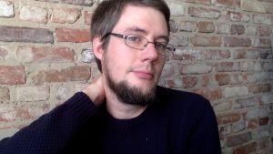 Fredrik Sonck i en svart tröja står framför en tegelvägg.