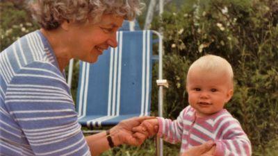 Hymyilevä isoäiti istuu nurmikolla ja pitää käsistä pientä hyväntuulista taaperoa, taustalla puutarhan kasveja ja tuoli.