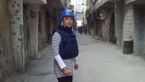 Nada Kettunen luotiliiveissä ja kypärä päässä Syyriassa fikserin työssä