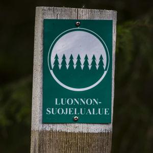 """En skylt med texten """"Luonnonsuojelualue"""" (naturskyddsområde)."""