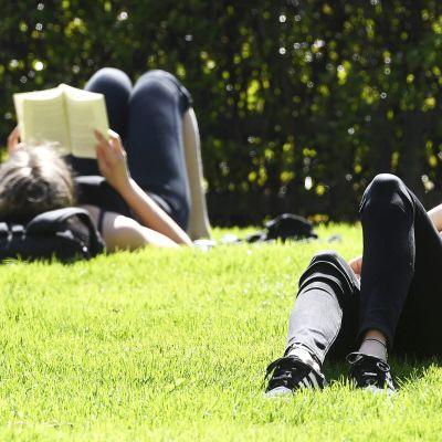 Ihmiset nauttivat kevätauringosta Esplanadin puistossa  Helsingissä.