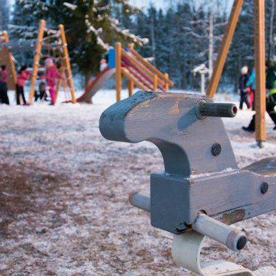 Koululaisia leikkimässä talvisella piha-alueella.