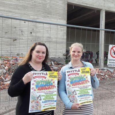 Naiset Ryttylän koulun edustalla pitelemässä julisteita