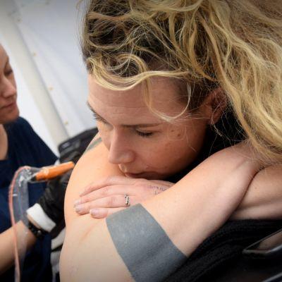 Säde Sonck tatuoi Jenni Ahtiaisen selkää