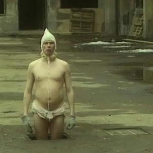 Jukka Rasila seisoo vaippa päällä hylätyssä tehtaassa.