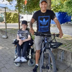 Poika pyörätuolissa ja nuori mies maastopyörän kanssa
