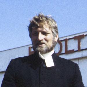 Tankki täyteen -sarjan roolihahmo rovasti, jota näyttelee Erkki Siltola.