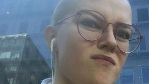 Michelle Jerkku grimaserar med hörlurar i öronen.