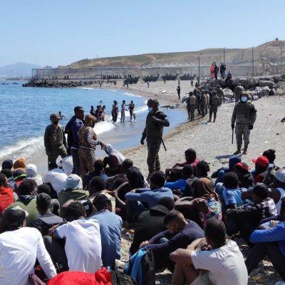 Suuri joukko siirtolaisia istuu rantahiekalla. Rannalla seisoo sotilaita varusteissaan, kasvomaskit päällä.