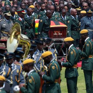 Militärer bär på en flaggbeklädd likkista.