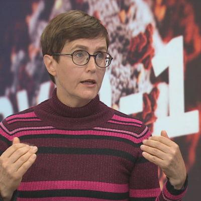 Psykolog Pilvikki Absetz i programmet Yles morgon. I bakgrunden en skärm med texten covid-19.