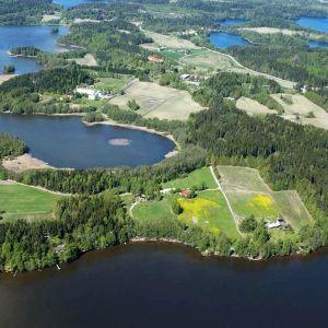 En flygbild av ett område som omges av vatten. Det syns skog, åkrar och enstaka hus och vägar. Sommar och sol.