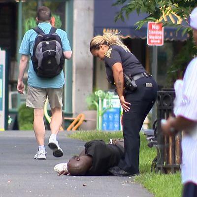 Poliisi auttamassa kadulla makaavaa ihmistä