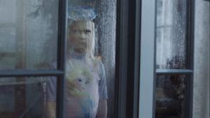 Vaaleahiuksinen tyttö katsoo ulos surullisena ikkunasta sateiseen säähän. Tytöllä on päällään isot uimalasit ja uimapuku.