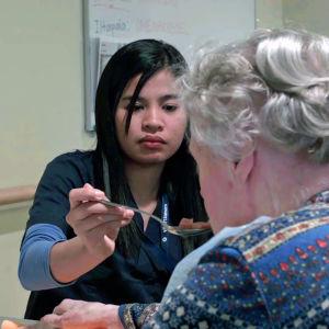 Filippiiniläinen Niezel Carolino syöttää iäkästä naista palveltalossa.