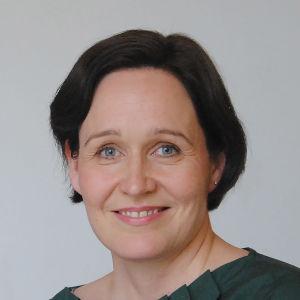 Riitta Birkstedt, en dam med mörkt hår och grön veckad skjorta.