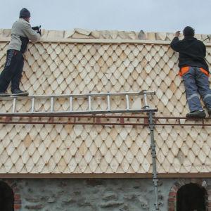 Kaksi miestä rakentaa kirkon paanukattoa.